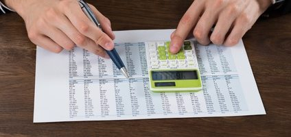 Close-up Of Businessperson Working With Accounting Document At Desk