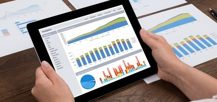 Close-up Of Person Hands Analyzing Financial Statistics Displayed On Digital Tablet